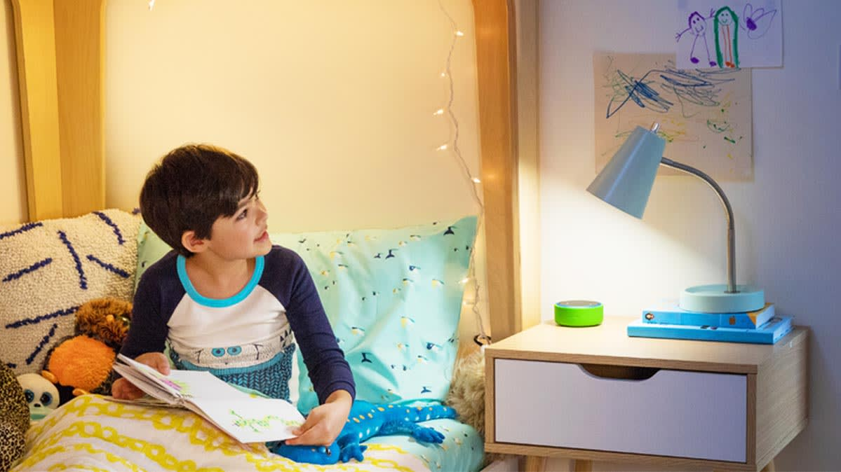 A child in a bed with an Echo Dot Kids speaker on the bedside table.