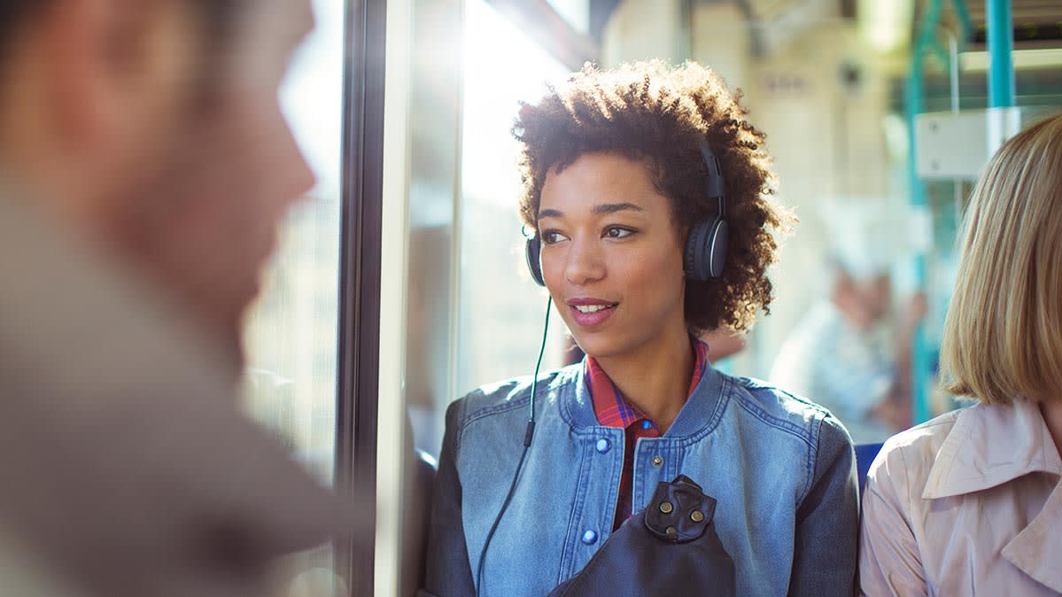 A woman wears headphones on a train. The best headphones under $200 are as easy on the ears as they are on your wallet.