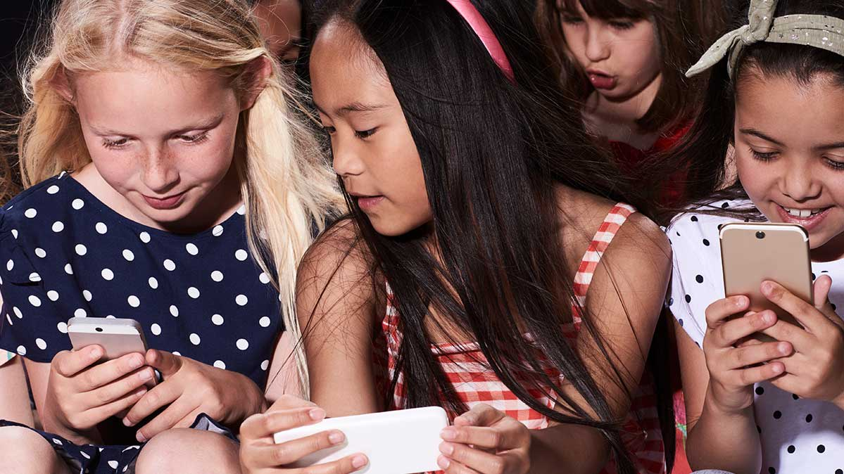 Young kids with phones for an article on educating kids about digital privacy.