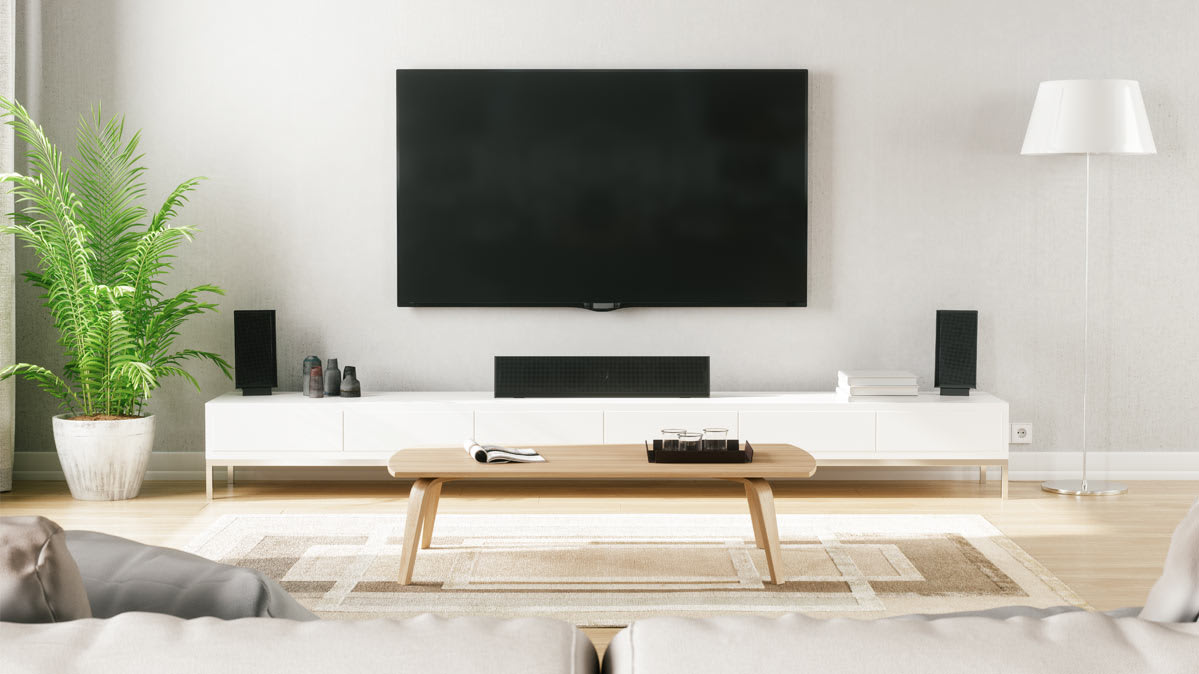 A TV that is part of a DIY Home Theater system hanging on a wall