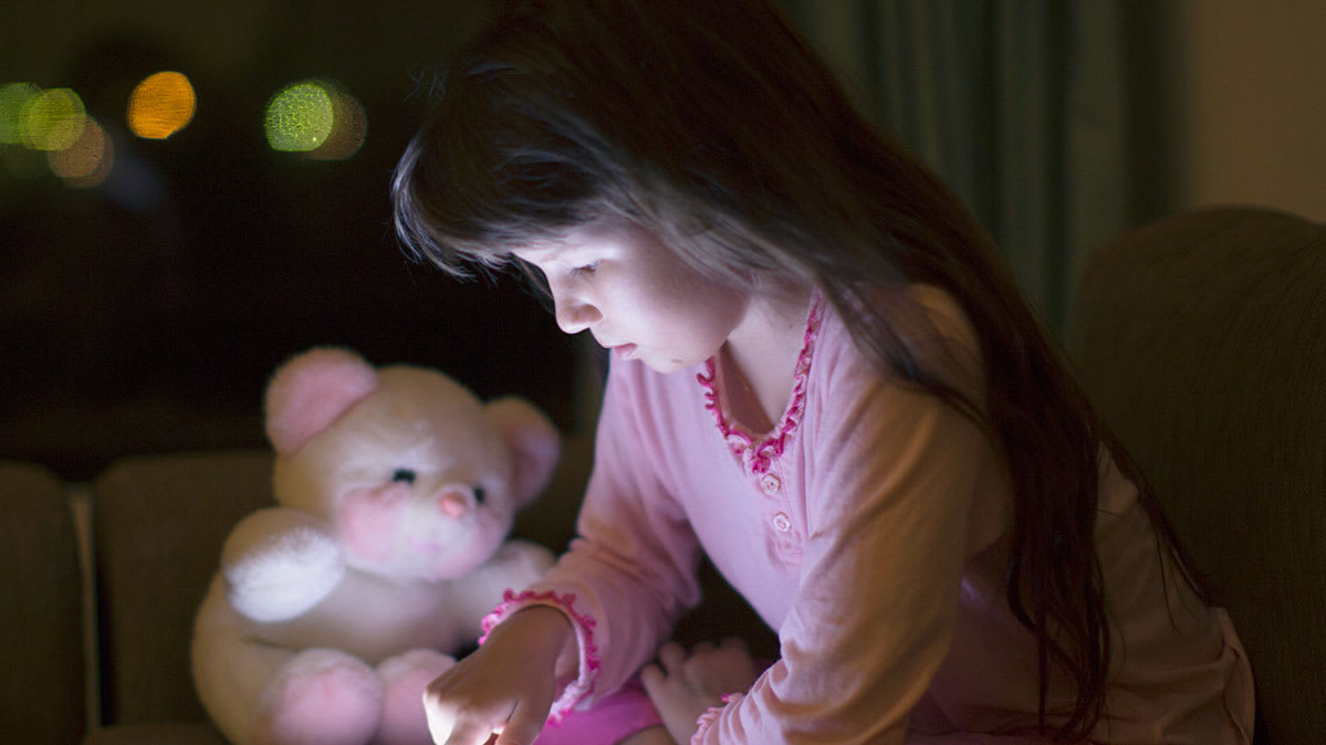 Connected toys being played with by a girl with a teddy bear visible. Such toys can have privacy risks.