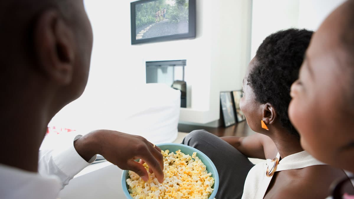 Photo of a family eating popcorn and watching a video streaming service.