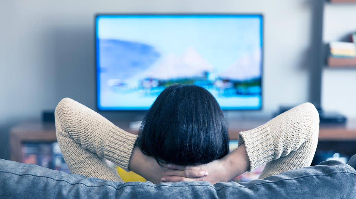 Picture Of A Person Sitting On A Sofa Looking At A TV For A Story On