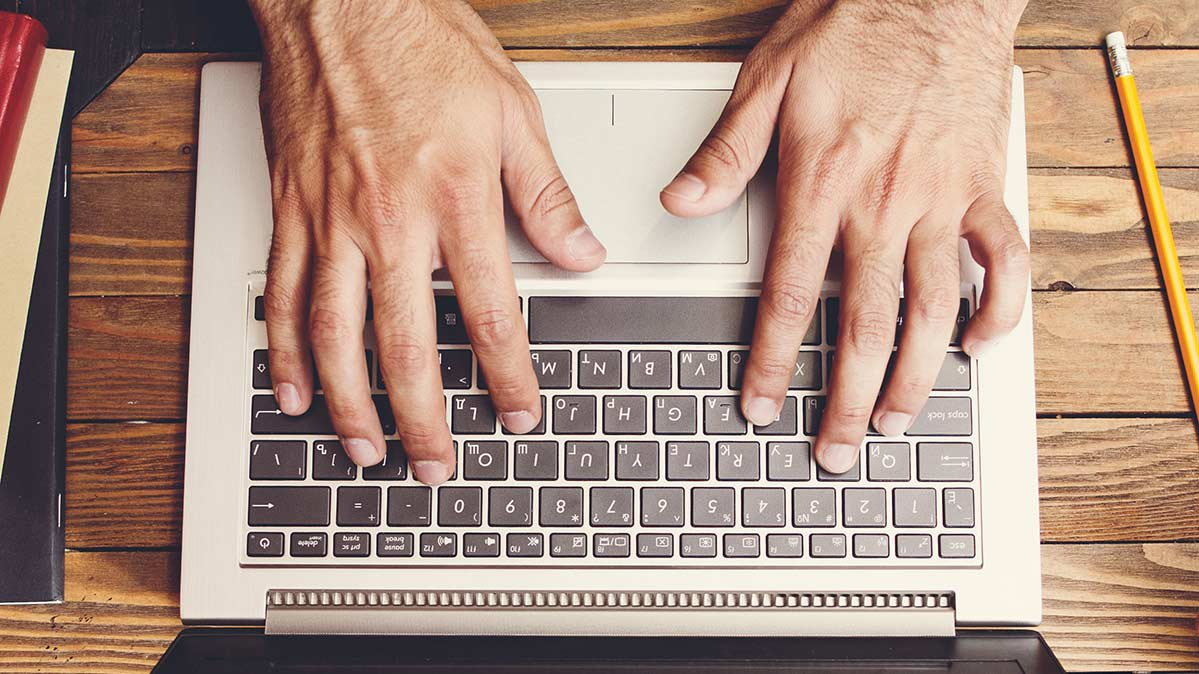 Hands typing on a laptop.