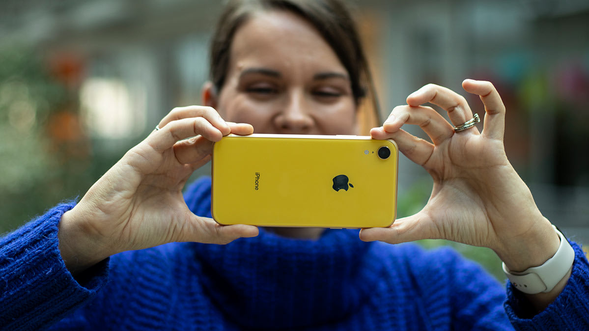 A woman takes a photo with an iPhone XR.
