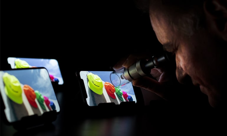 Claudio Ciacci, who oversees TV testing at Consumer Reports, studies the pixels in the new iPhones' screens.