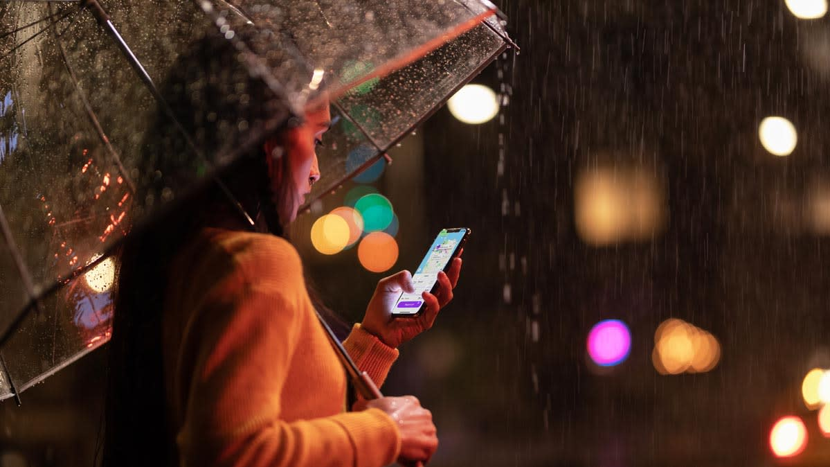 A Woman Standing Under An Umbrella Looking At Her Iphone