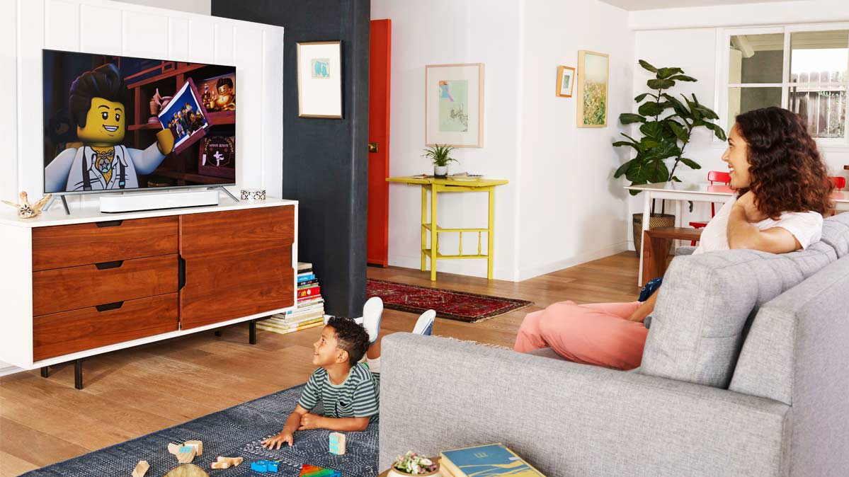 A family watching a TV with a sound bar speaker.
