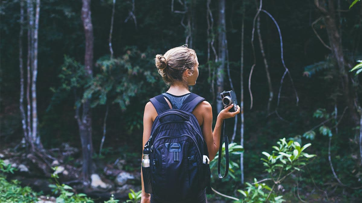 A woman hikes in the woods.