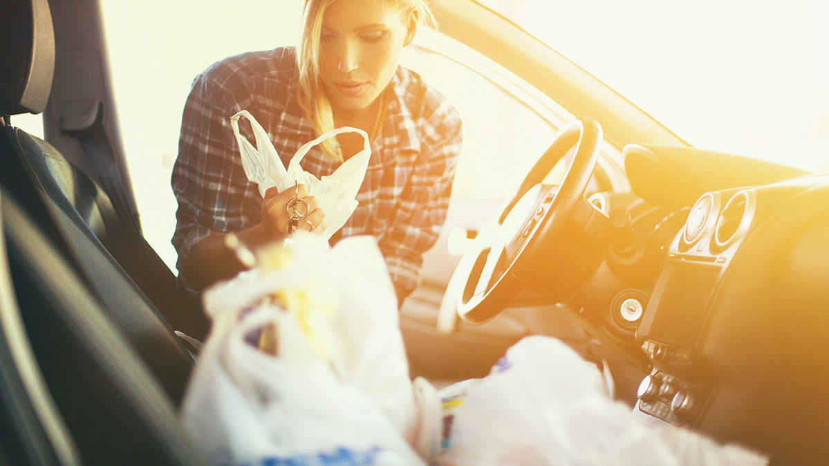We have tips for keeping your food safe in a hot car. Pictured: Woman unloading groceries.