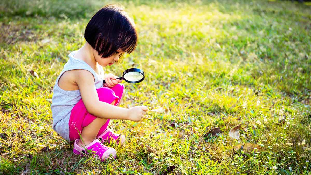 A young child plays in the grass.