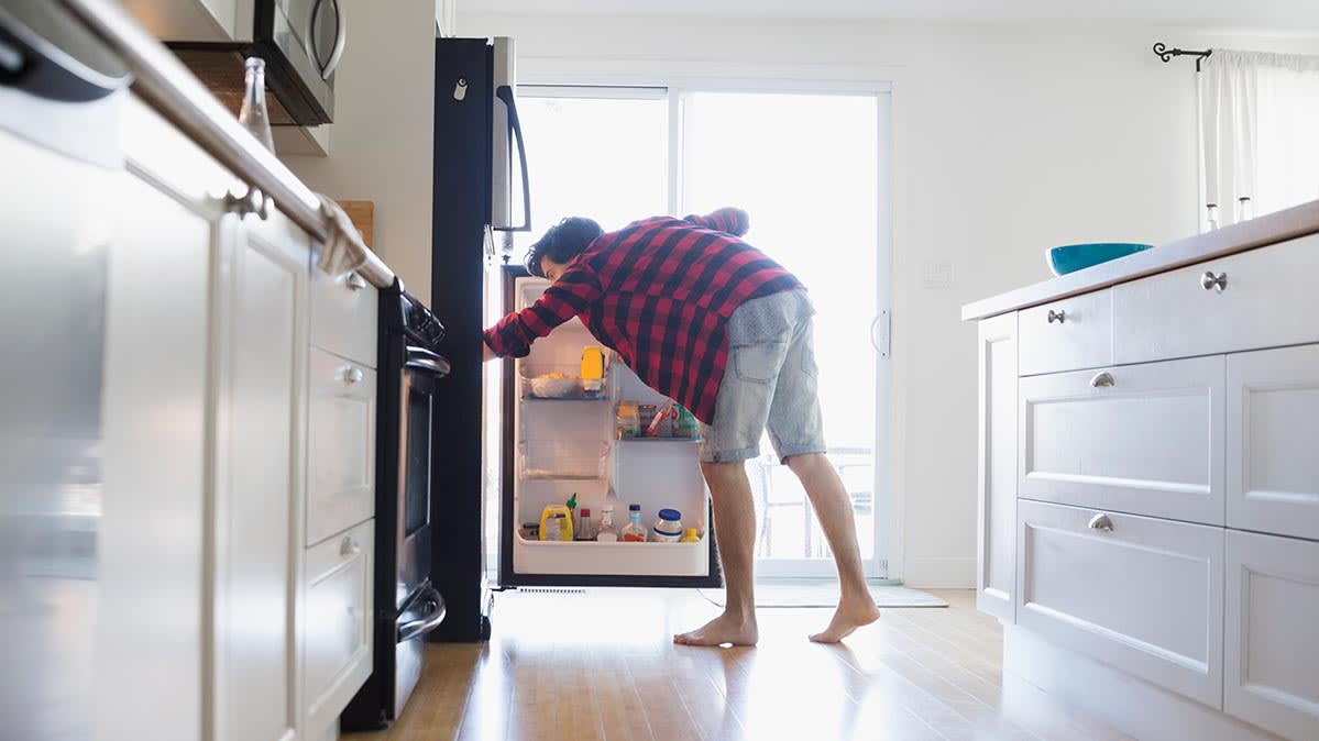 A man bends over to look in a top-freezer refrigerator