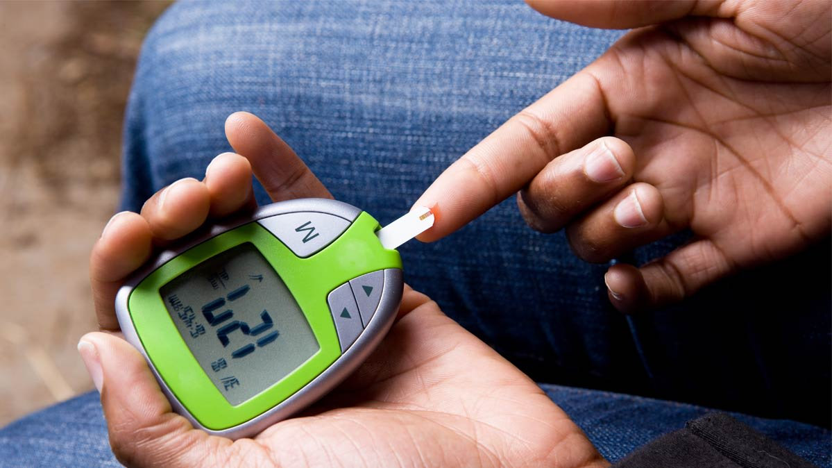 A person tests their blood sugar using a blood glucose meter.