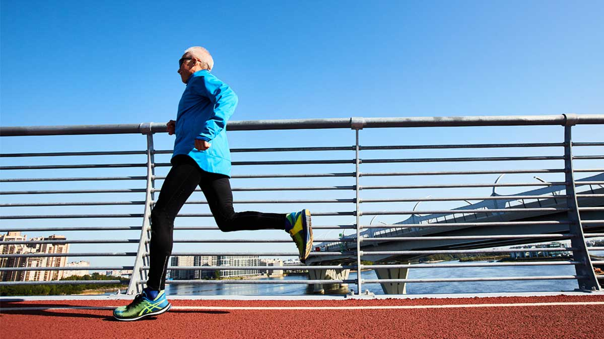 Man in blue shirt, black pants, and sneakers running outside on a track.