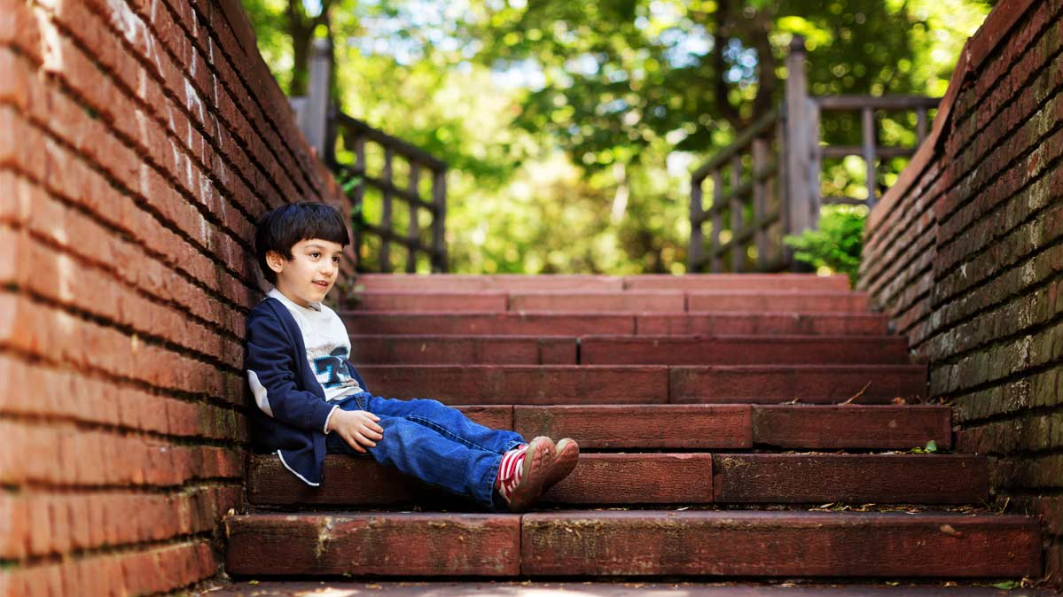 A child sits on brick steps outside.