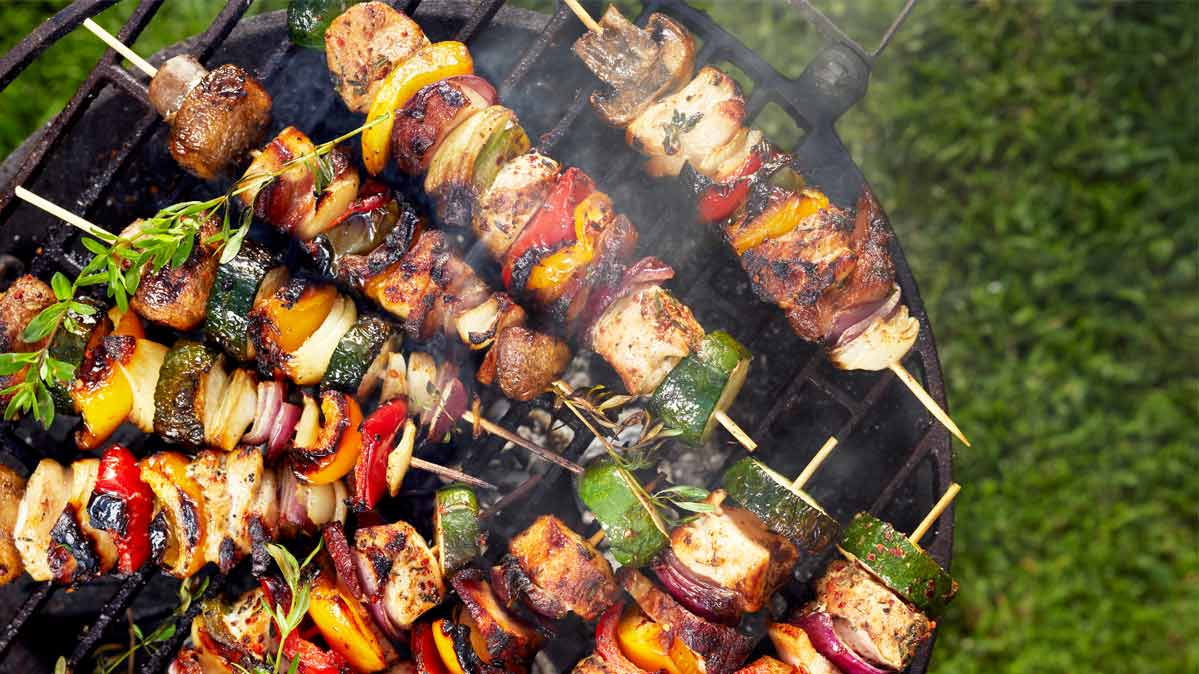 Veggie/meat kebobs on a grill.