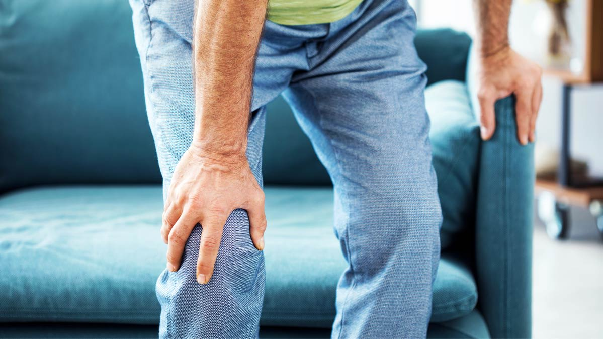 Man holding a knee as if in pain.