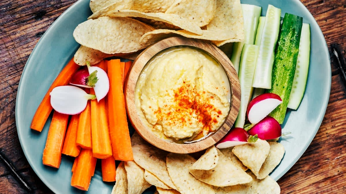 A plate of hummus, vegetables, and chips. Hummus is a healthy dip.
