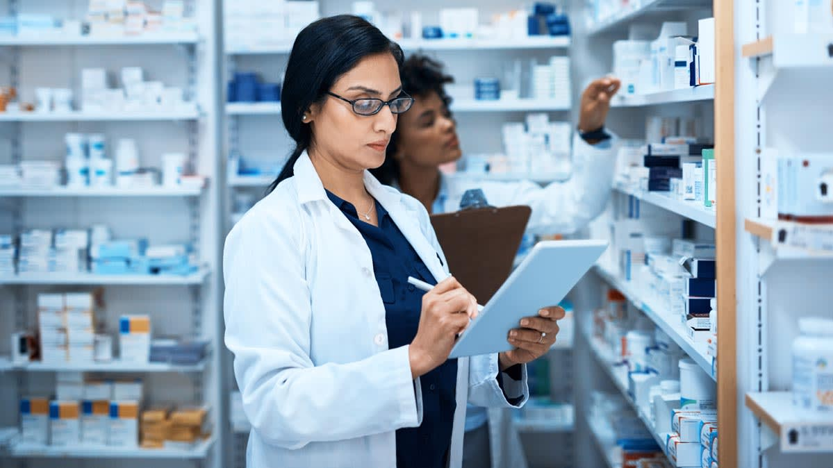 Two female pharmacists checking medication stock in a drugstore.