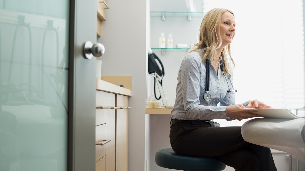 A physician sits at a desk.