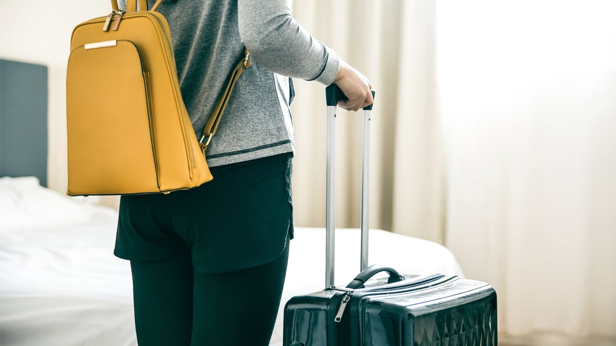 A person with luggage standing in a hotel room.