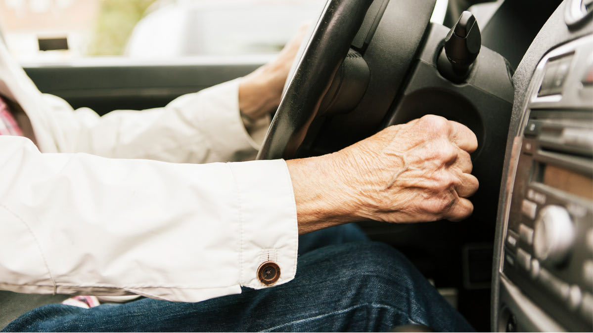 A senior driver with one hand on the steering wheel and the other hand is starting the car.