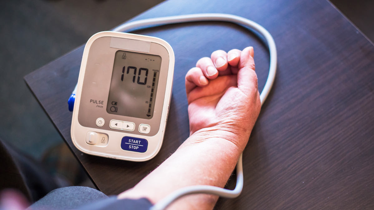 A person tests their blood pressure with a home blood pressure monitor