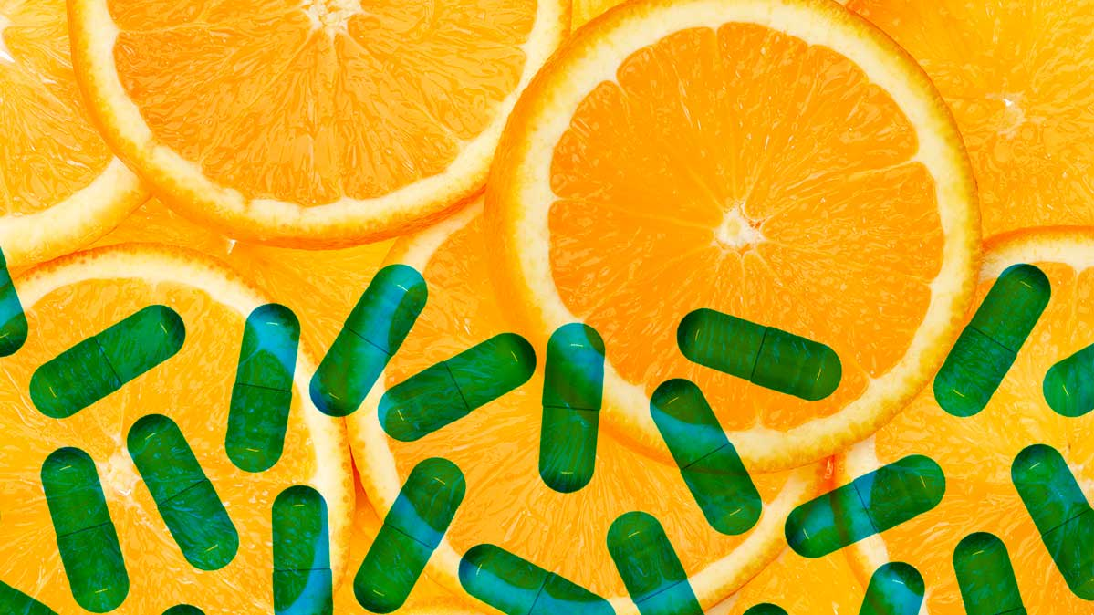 green capsules of medication and slices of oranges