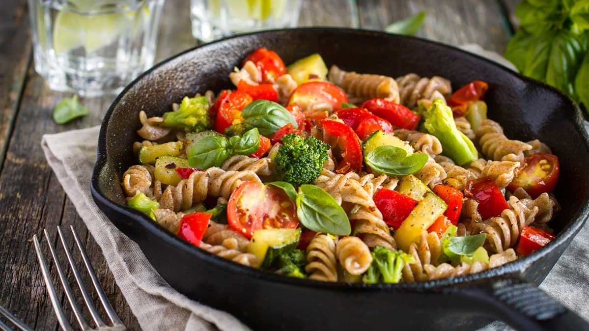 A pan of pasta topped with broccoli and tomatoes.