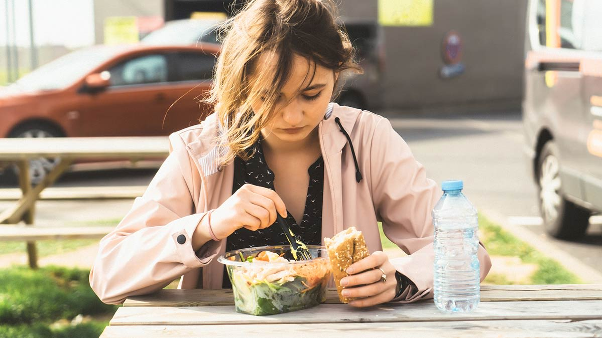 Young woman eats a ready-made salad on a picnic table.