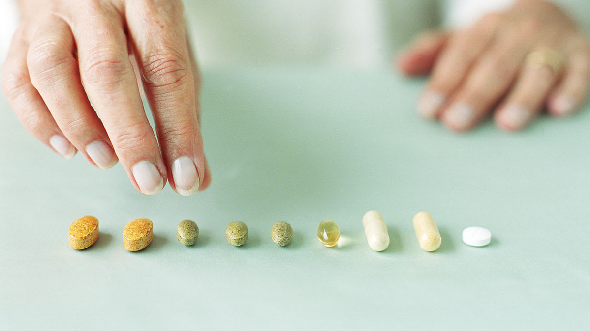 A person selecting a pill from a group of medicine and supplements