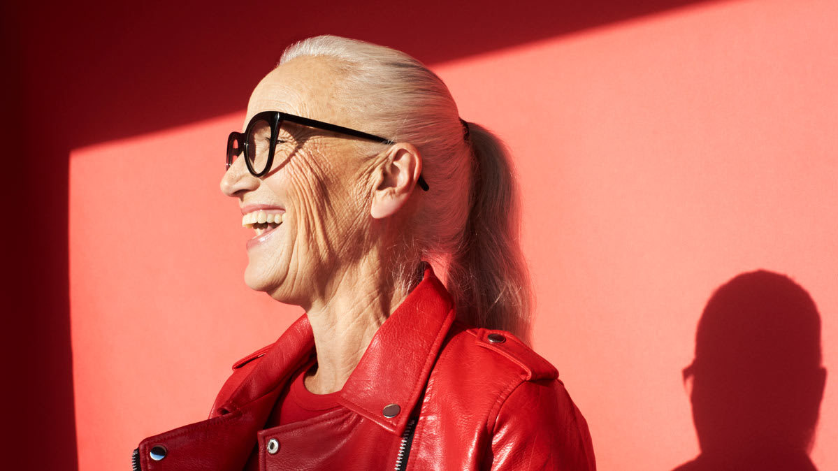 Older woman wearing red leather jacket and black rimmed glasses smiling widely.