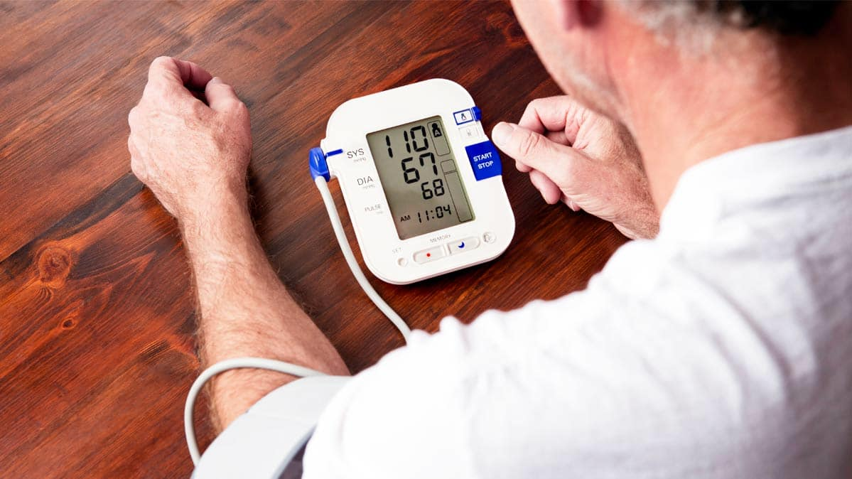 A man using a blood pressure monitor.