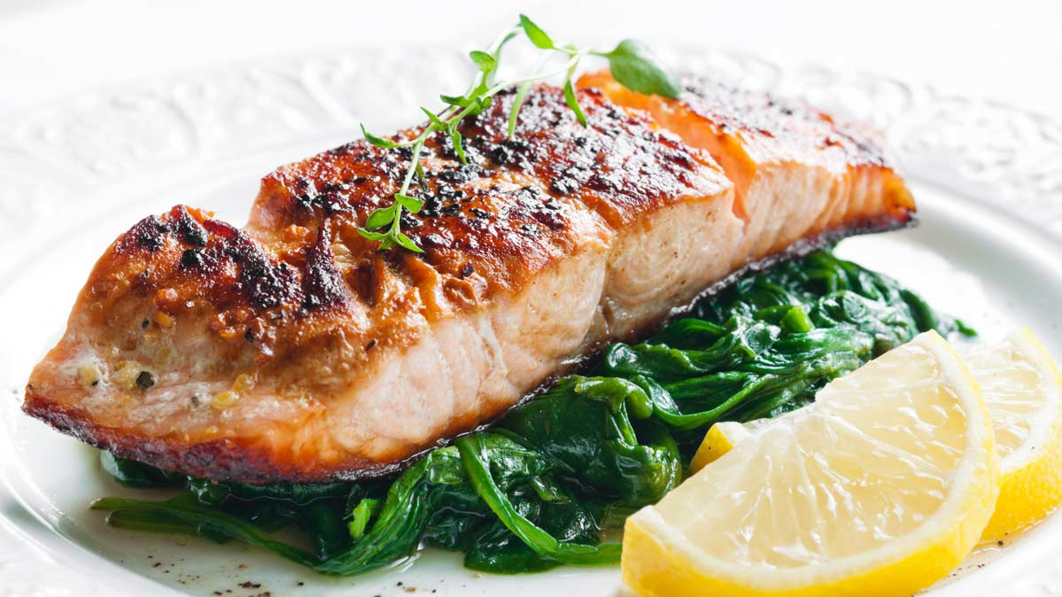Salmon on a bed of greens, which may reduce risk of peripheral artery disease.