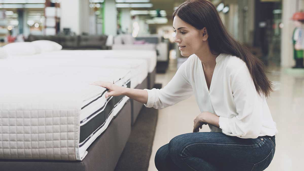 Shopper examining mattress in showroom