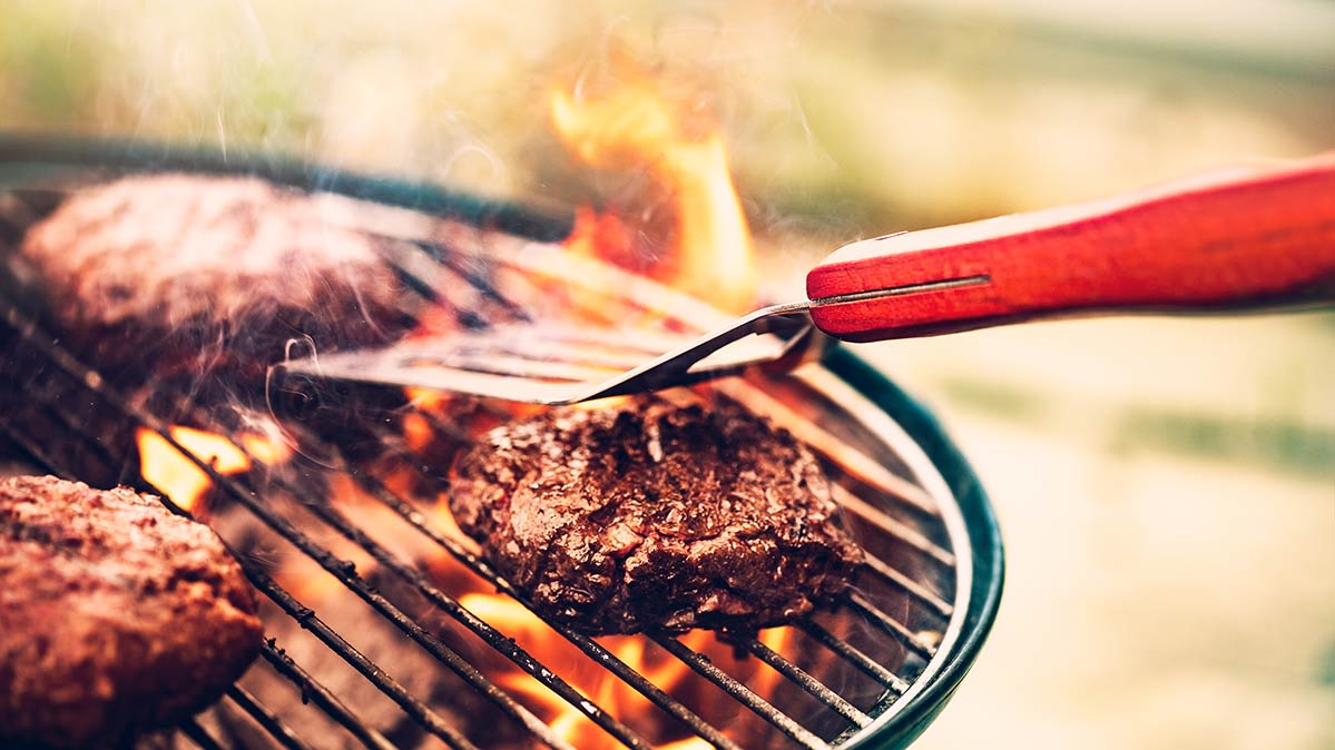 A Burger Being Cooked On One Of The Best Charcoal Grills From Consumer Reports Tests
