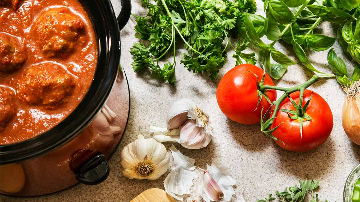 A slow cooker with food cooking in it, surrounded by tomatoes, parsley, and garlic.