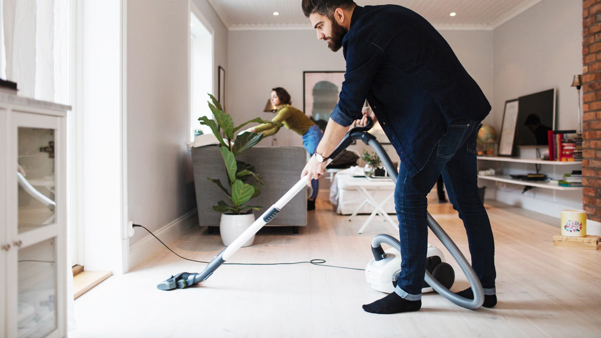 A man using a canister vacuum while doing house work