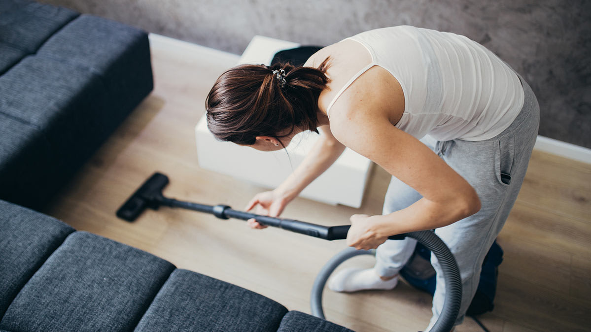 A woman vacuuming with a bagless vacuum.