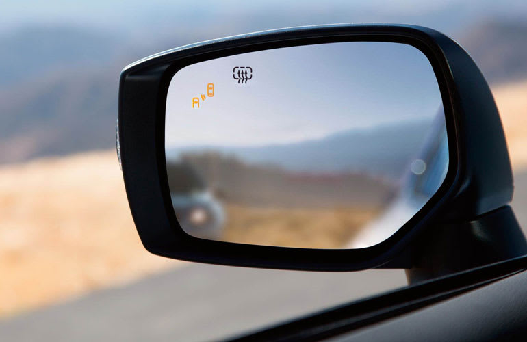 A sideview mirror with icons to indicate car features such as blind-spot monitoring.