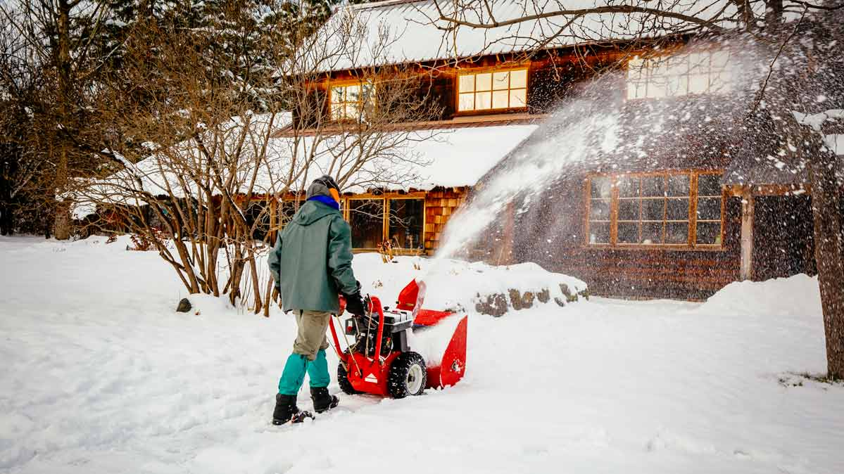 A person using a snow blower to clear their driveway.