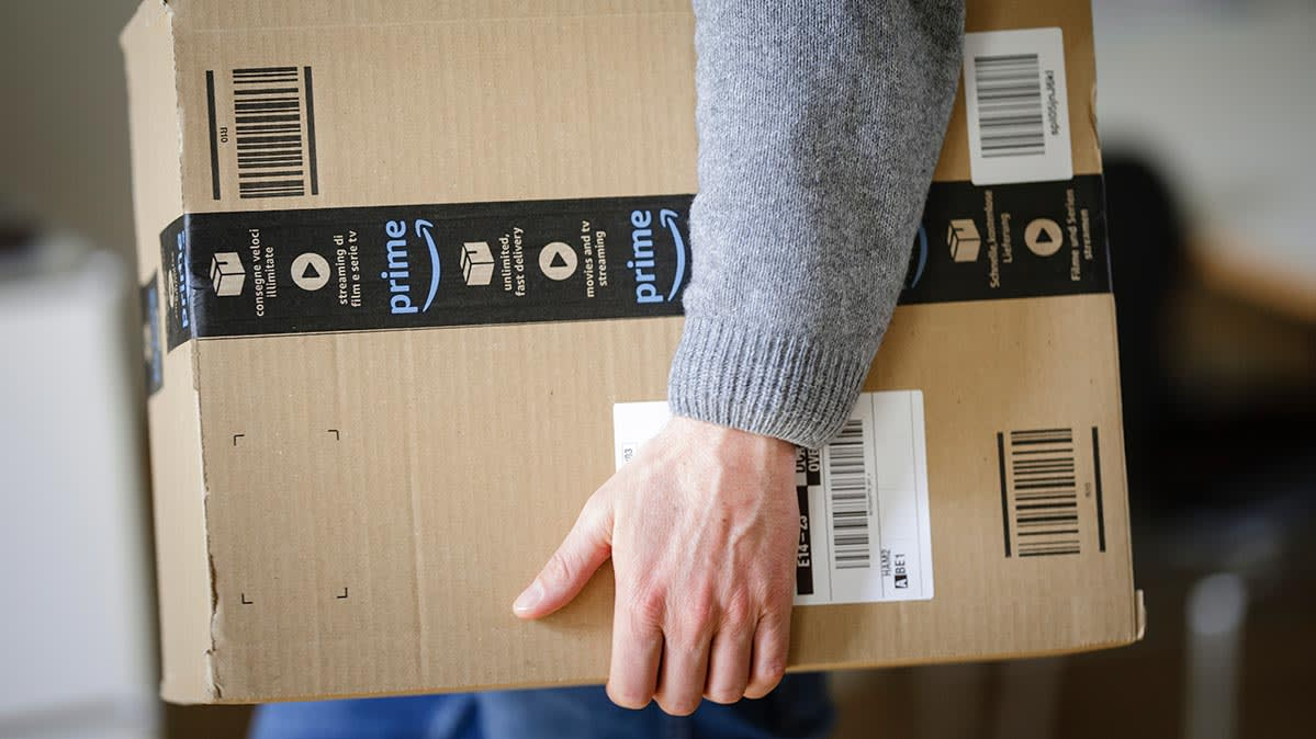 A person holding an Amazon Prime package.