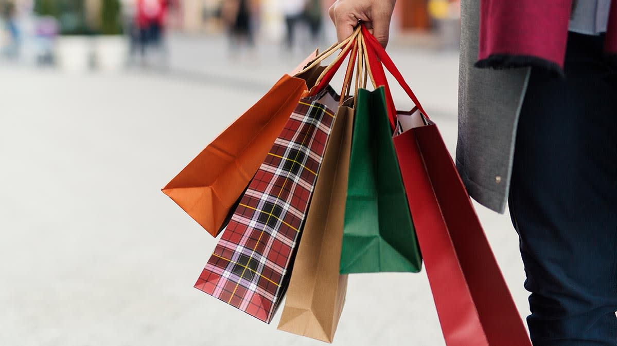 A person holding shopping bags while doing holiday shopping