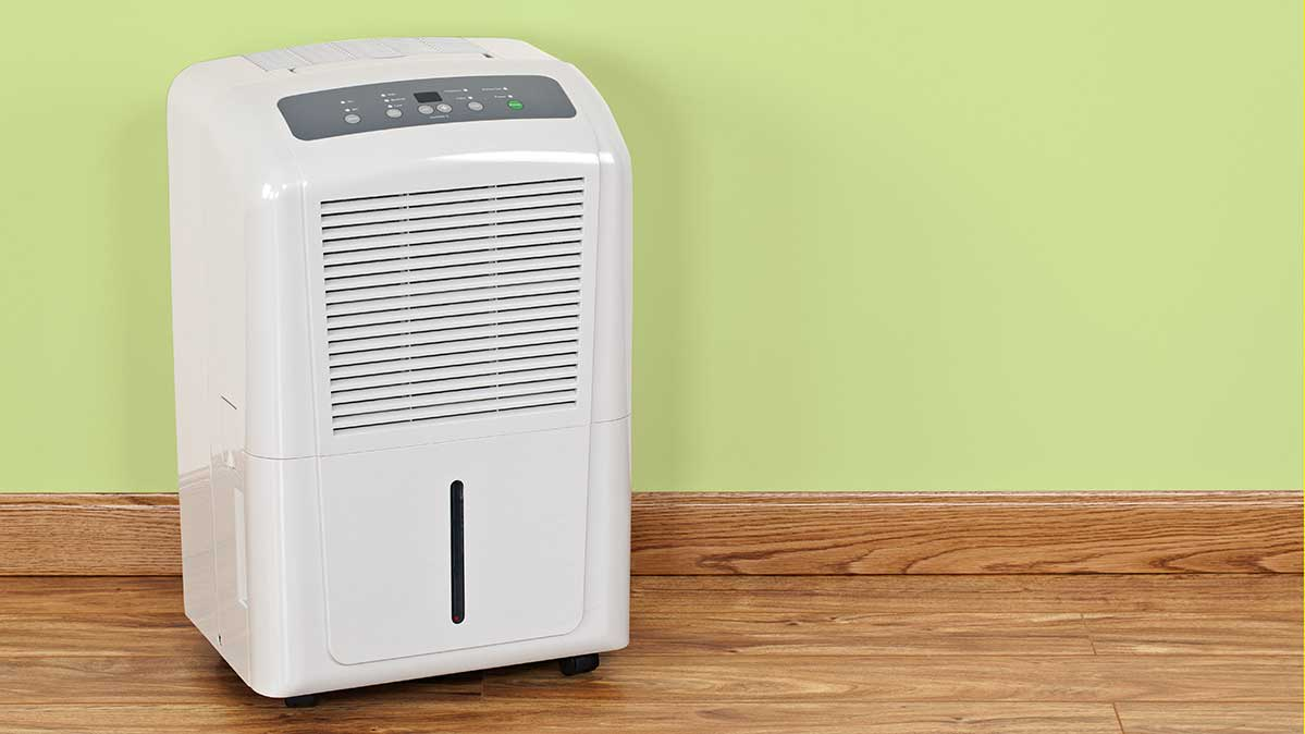 A dehumidifier on the floor of a dining room. Humidifiers are among the products on deep discount in July.