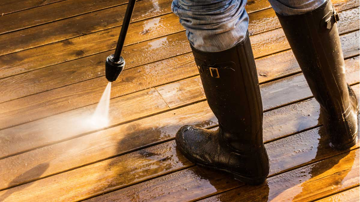 A person wearing boots using a pressure washer on a deck.