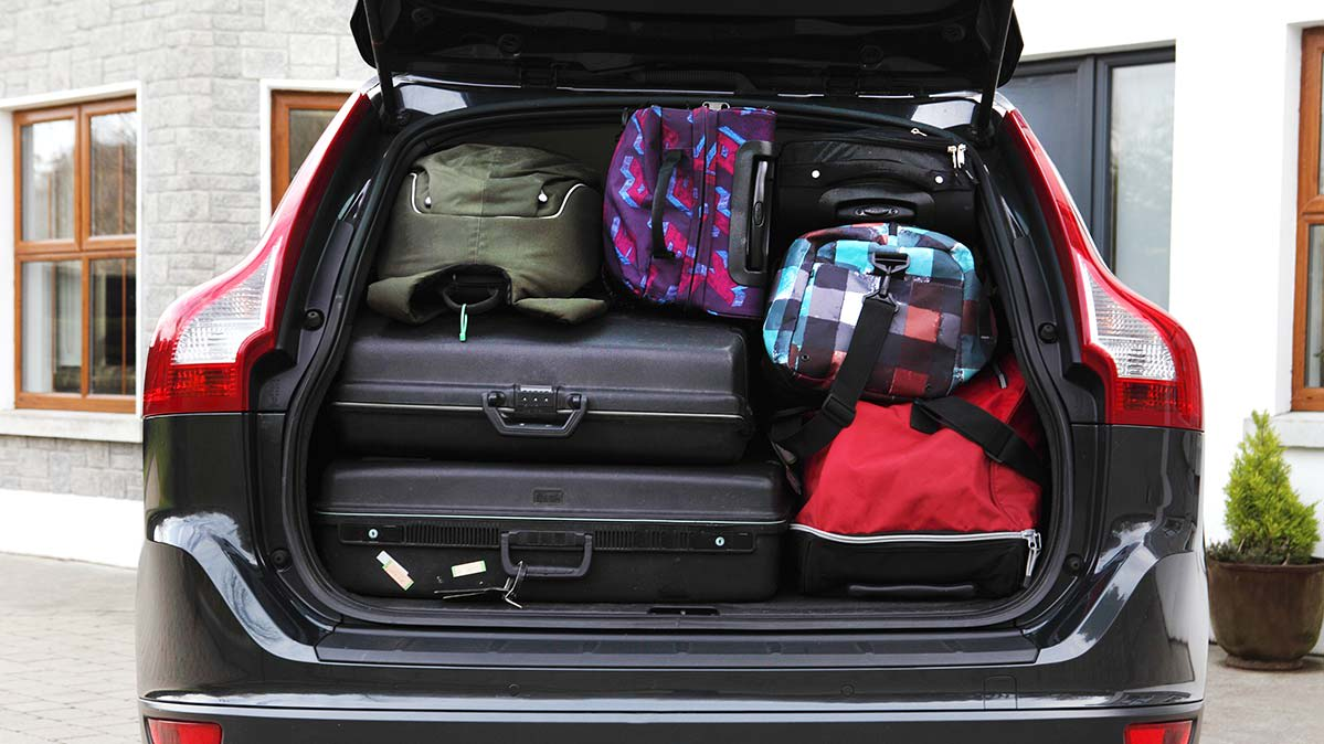 A car packed with soft-sided and hard-sided luggage.