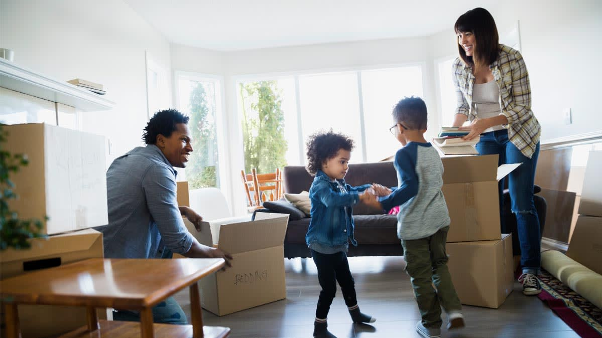 Parents unpacking boxes while children dance