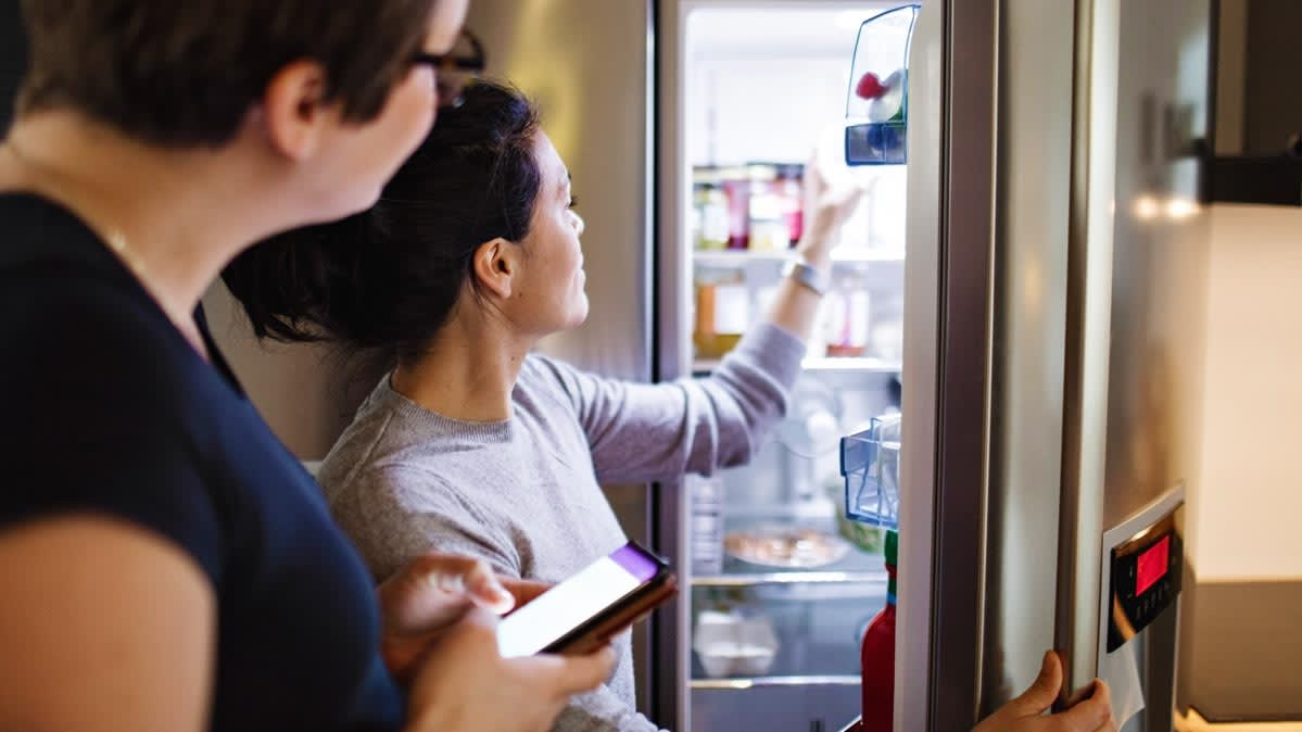 Two women look inside a refrigerator.