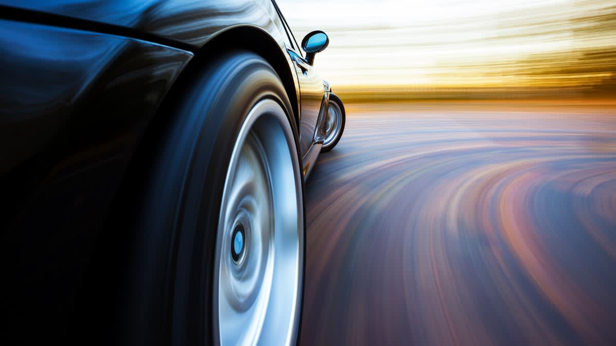 Photo of a car going around a turn for article on tire care.