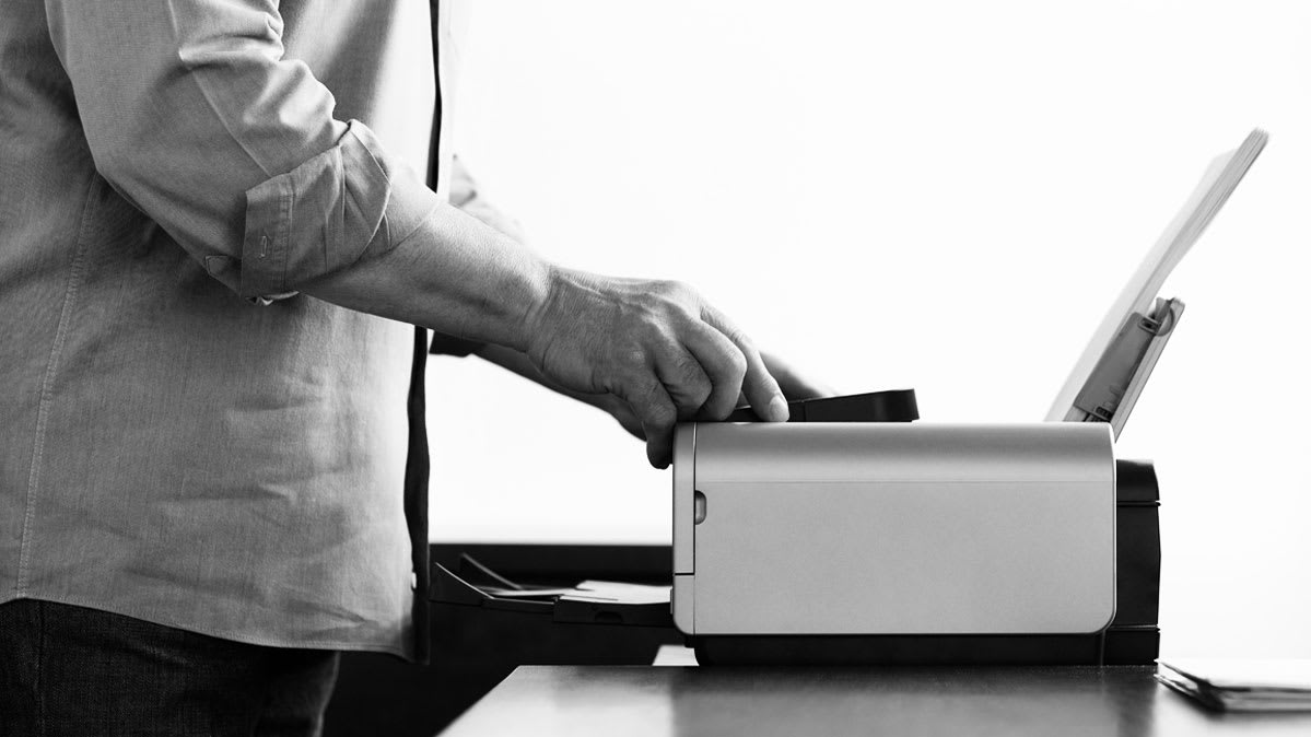 A man loading a new ink cartridge into a printer for article on printer reliability.